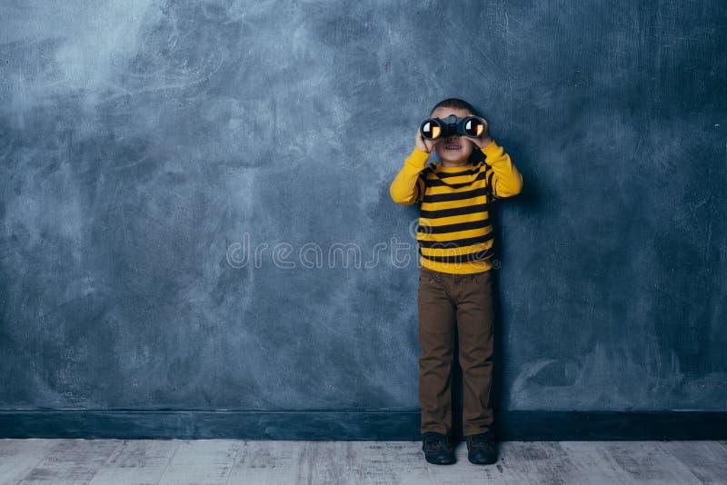 Rapaz pequeno que olha atrav?s dos bin?culos em um escuro - fundo azul com uma posi??o feliz da cara imagens de stock