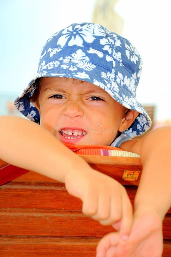 Rapaz pequeno que olha de sobrancelhas franzidas fotografia de stock royalty free