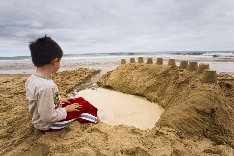 Rapaz pequeno que olha o mar imagens de stock royalty free