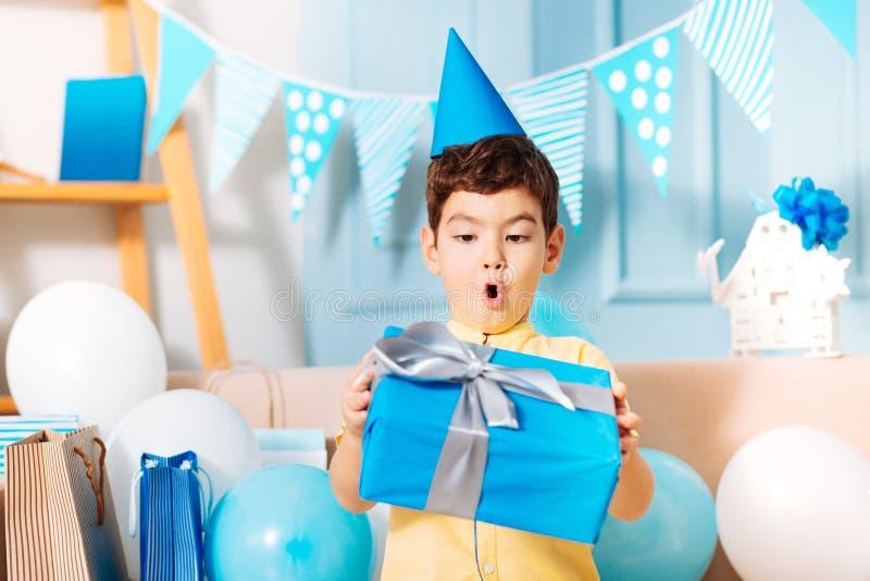 Rapaz pequeno que olha seu presente de aniversário com surpresa fotografia de stock