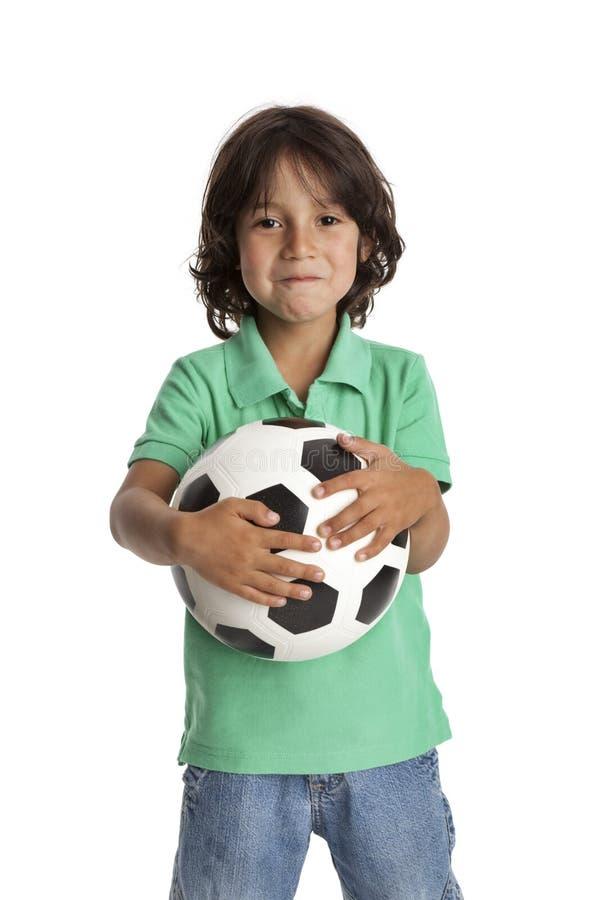 Rapaz pequeno que prende uma esfera de futebol fotos de stock royalty free