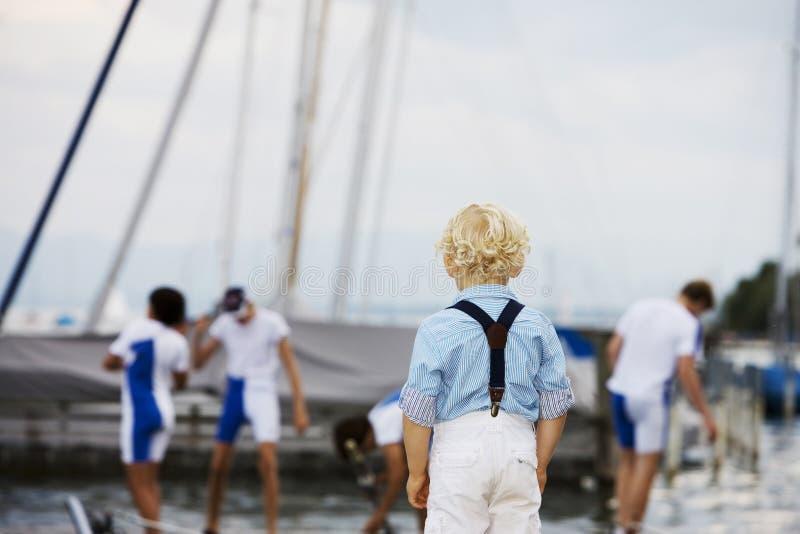 Rapaz pequeno que presta atenção a sua equipe de esportes favorita imagem de stock