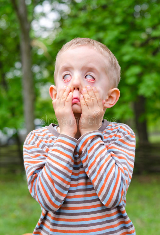 Rapaz pequeno que puxa uma expressão assustador foto de stock royalty free