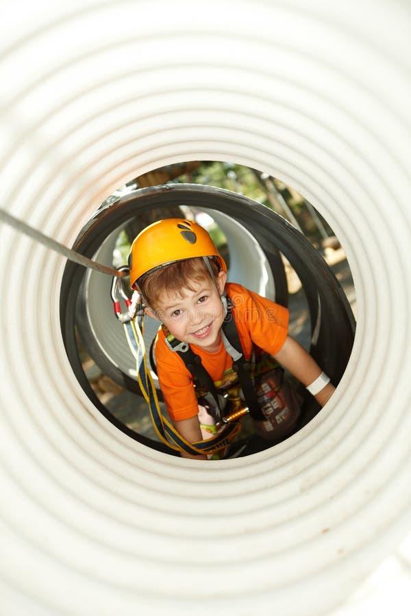 Rapaz pequeno que rasteja no parque da aventura imagem de stock