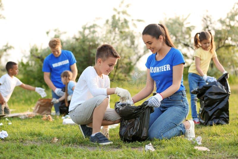 Rapaz pequeno que recolhe o lixo com voluntário foto de stock