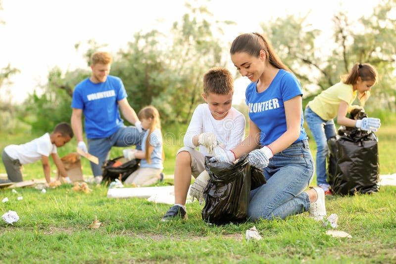Rapaz pequeno que recolhe o lixo com voluntário imagem de stock royalty free