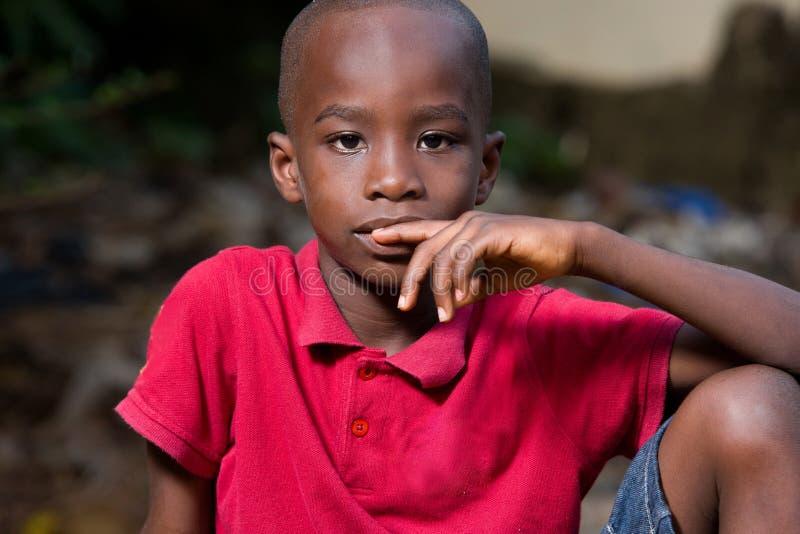 Rapaz pequeno que senta-se apenas e pensativo fotografia de stock royalty free