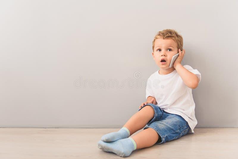 Rapaz pequeno que senta-se com o smartphone no estúdio imagem de stock royalty free