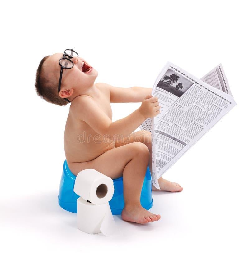 Rapaz pequeno que senta-se em potty com jornal fotografia de stock royalty free