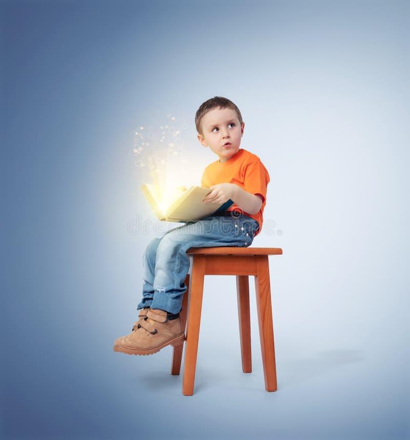 Rapaz pequeno que senta-se em uma cadeira com um livro mágico aberto, no fundo azul Conceito do conto de fadas imagens de stock