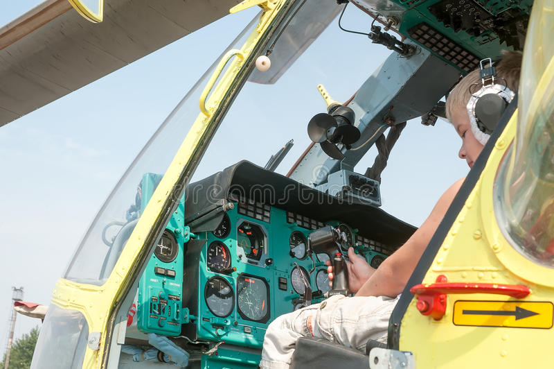Rapaz pequeno que senta-se na cabine do helicóptero MI-8 fotografia de stock