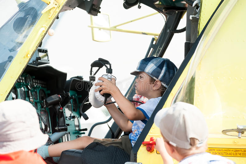 Rapaz pequeno que senta-se na cabine do helicóptero MI-8 foto de stock royalty free