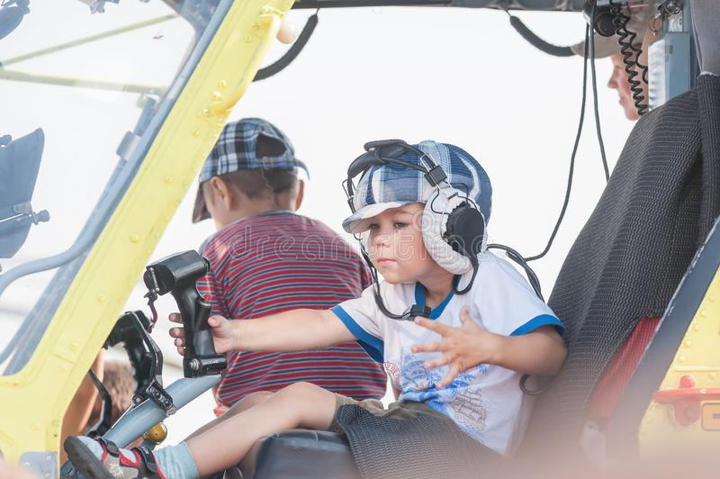 Rapaz pequeno que senta-se na cabine do helic?ptero MI-8 fotografia de stock royalty free