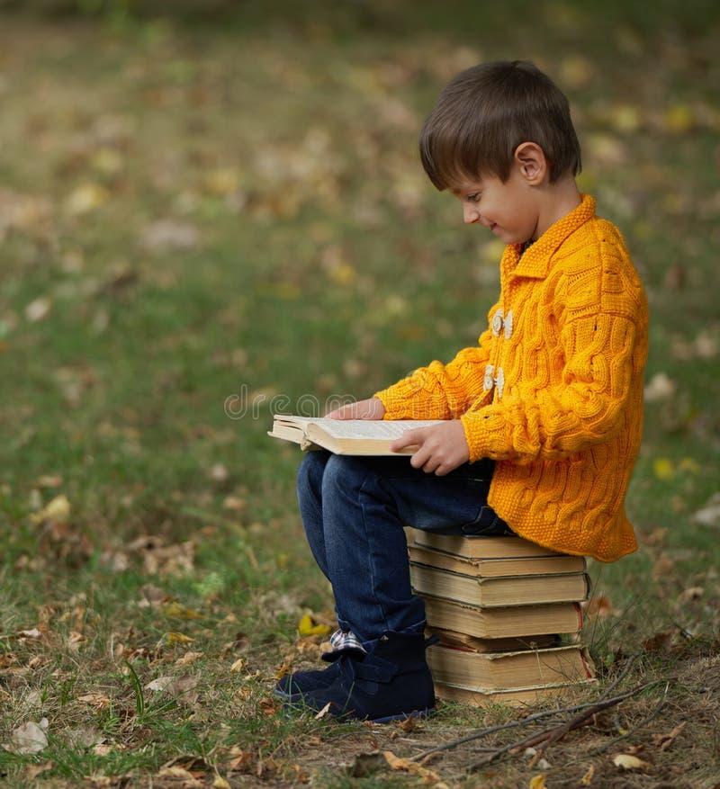 Rapaz pequeno que senta-se na pilha de livros fotos de stock