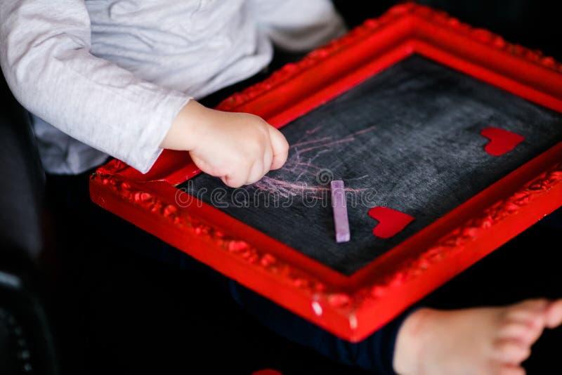 Rapaz pequeno que senta-se na poltrona com imagem quadro vermelha no St Valentine& x27; dia de s P?s pequenos do close-up fotografia de stock