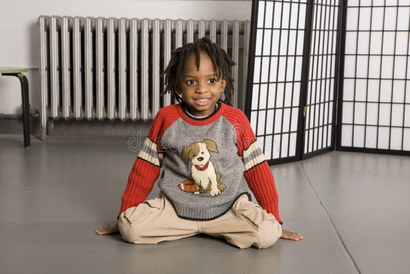 Rapaz pequeno que senta-se no assoalho imagem de stock royalty free