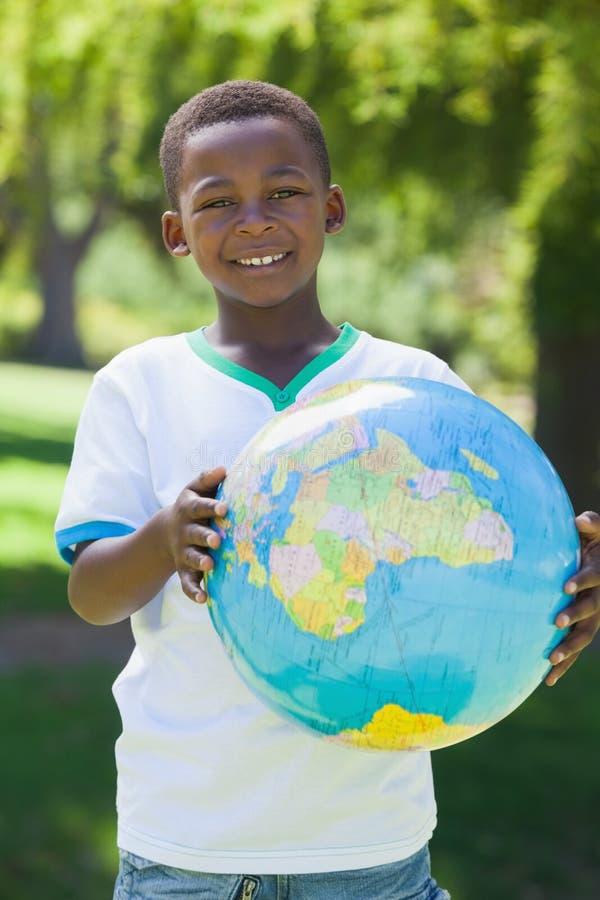Rapaz pequeno que sorri na câmera que guarda o globo no parque fotografia de stock