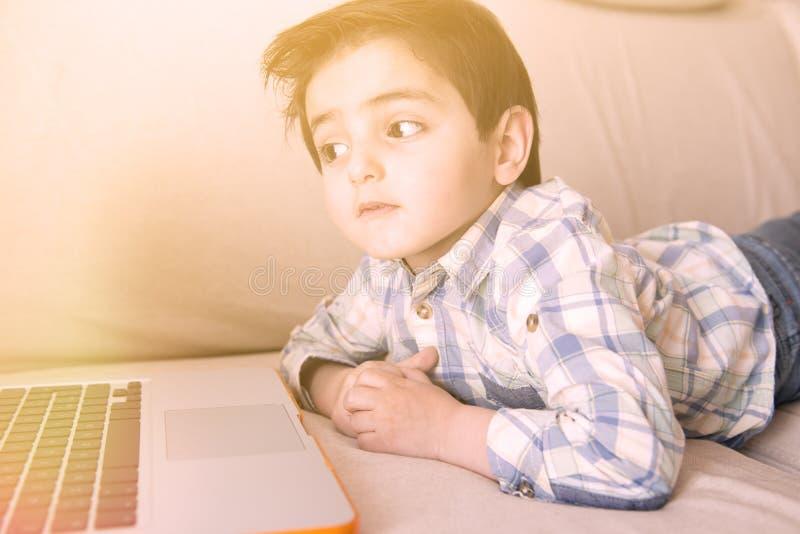 Rapaz pequeno que surfa em seu portátil imagem de stock