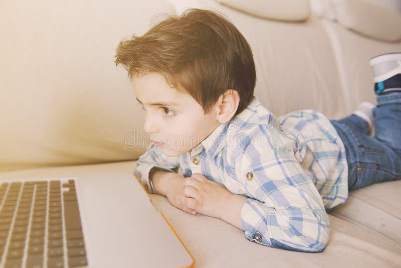 Rapaz pequeno que surfa em seu portátil imagens de stock