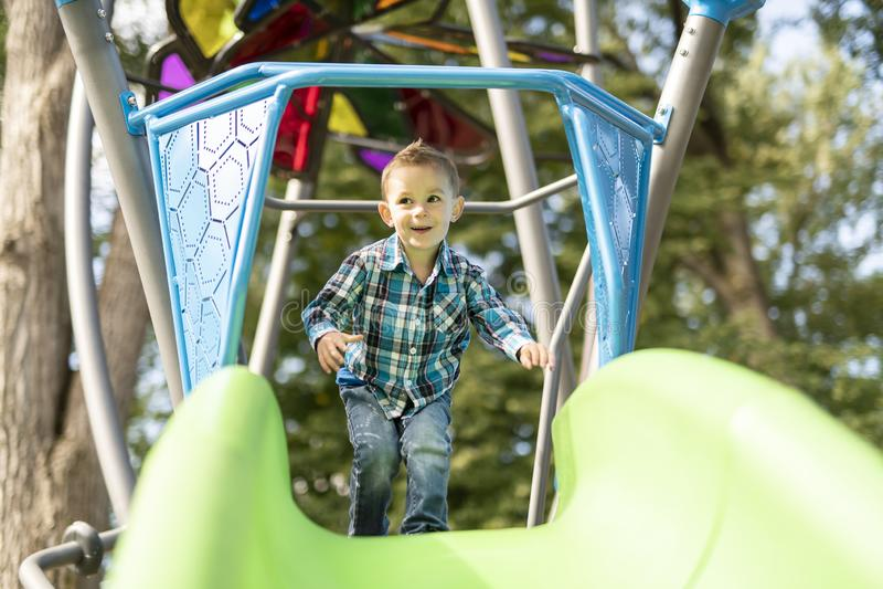 Rapaz pequeno que tem o divertimento em um campo de jogos fora no verão Criança em uma corrediça imagens de stock