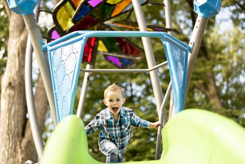 Rapaz pequeno que tem o divertimento em um campo de jogos fora no verão Criança em uma corrediça foto de stock royalty free