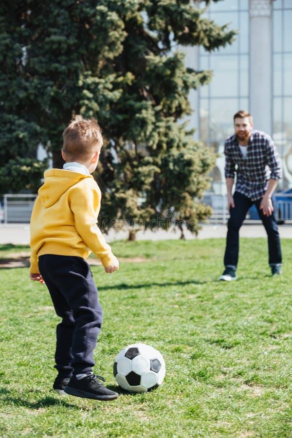 Rapaz pequeno que tem o divertimento jogando o futebol com seu paizinho fotos de stock