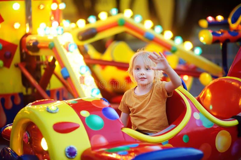 Rapaz pequeno que tem o divertimento no parque da atração em público A equitação da criança em um alegre vai círculo na noite do  imagem de stock royalty free