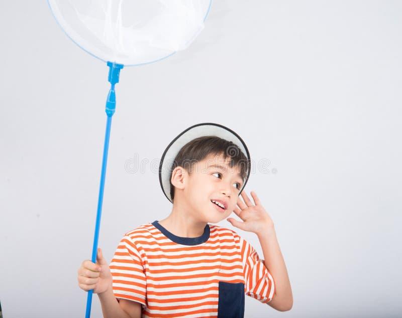 Rapaz pequeno que toma a inseto as atividades exteriores líquidas no fundo branco fotos de stock