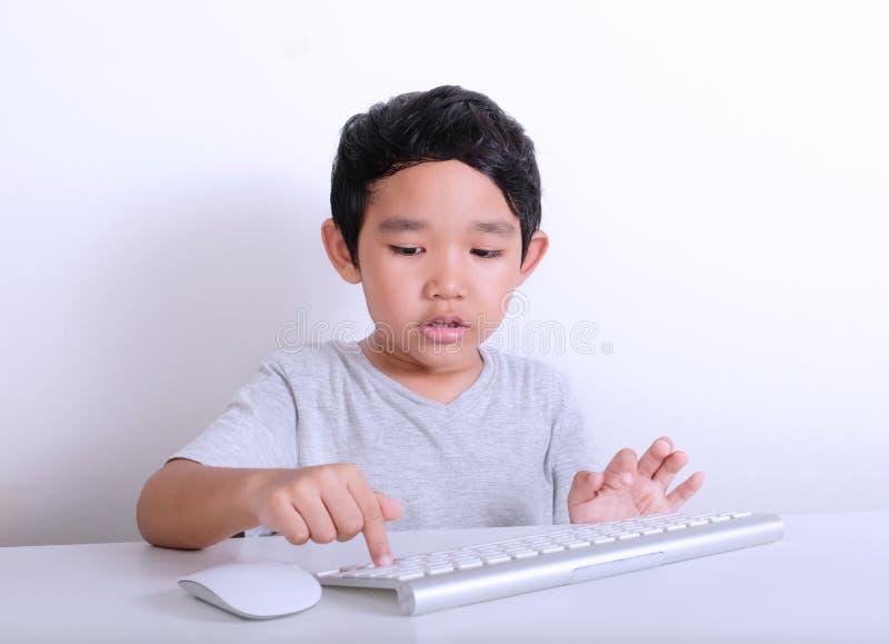 Rapaz pequeno que trabalha no computador fotografia de stock