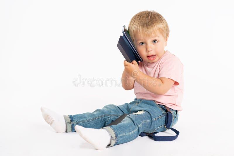 Rapaz pequeno que usa o telem?vel Crian?a que joga no smartphone Tecnologia, apps móveis, crianças e consultivo parental imagem de stock royalty free