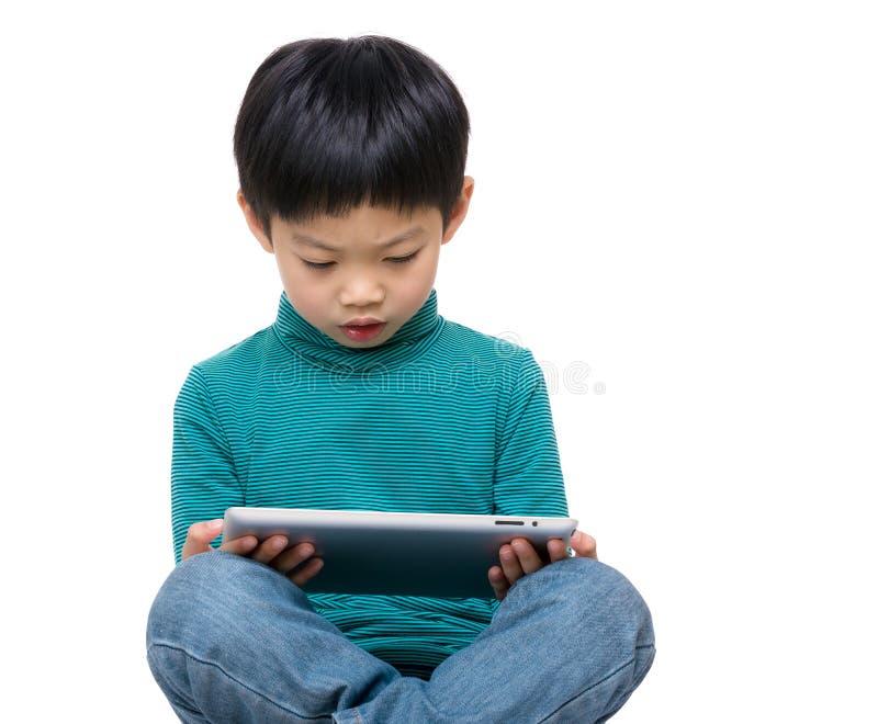 Rapaz pequeno que usa a tabuleta fotos de stock royalty free