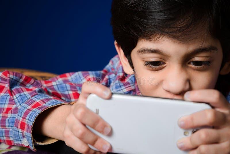 Rapaz pequeno que usa um Smart-telefone fotografia de stock royalty free
