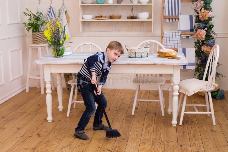 Rapaz pequeno que varre o assoalho Menino bonito que limpa a cozinha w fotos de stock royalty free