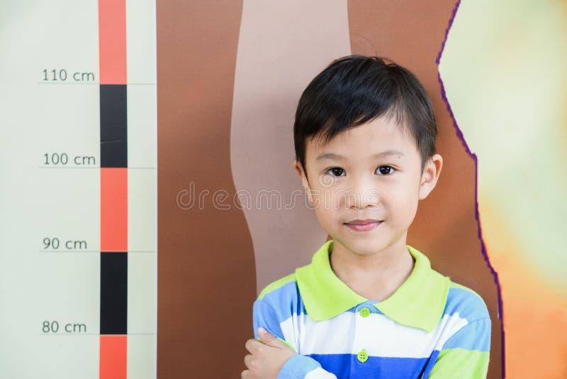 Rapaz pequeno que verifica sua altura na escola com a escala de medição da altura na parede só Medidas bonitos de sorriso do meni foto de stock royalty free