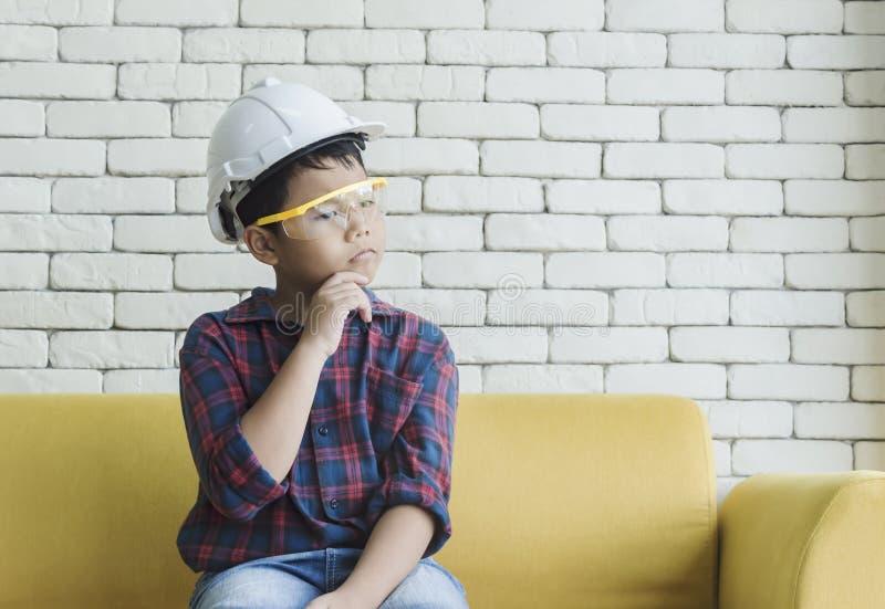 Rapaz pequeno que veste um capacete da engenharia e que olha durante todo a janela imagens de stock royalty free