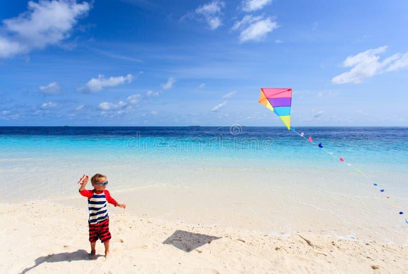 Rapaz pequeno que voa um papagaio na praia tropical fotografia de stock royalty free