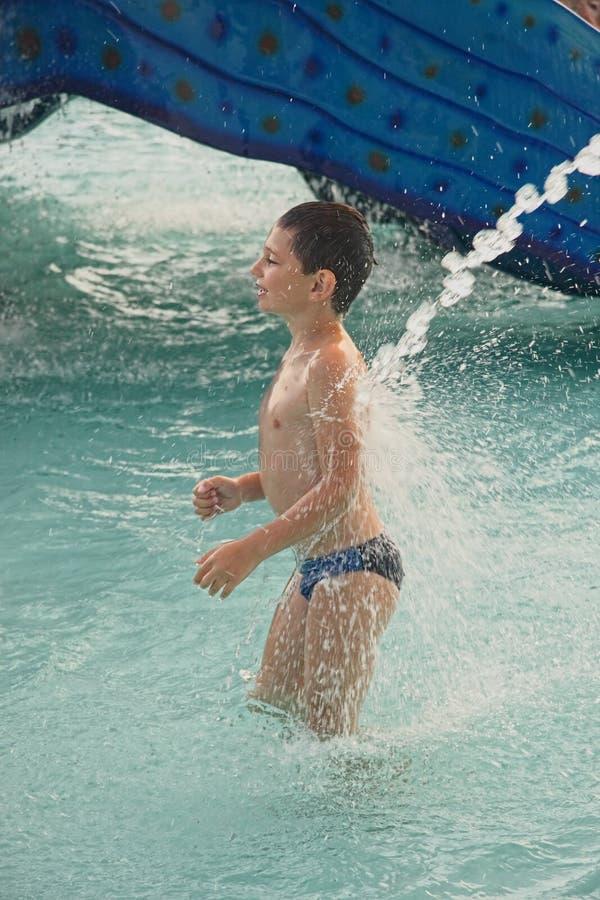Rapaz pequeno sob o jato de água imagem de stock royalty free