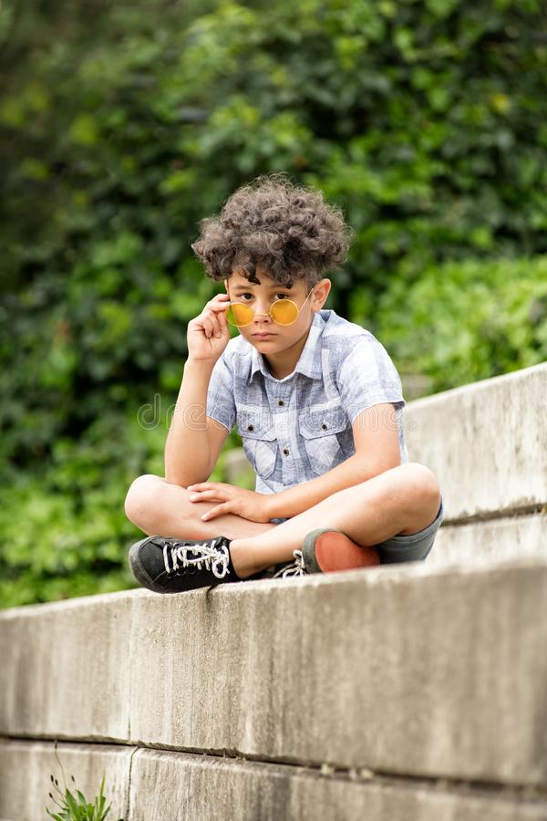 Rapaz pequeno solene que veste ?culos de sol amarelos imagens de stock
