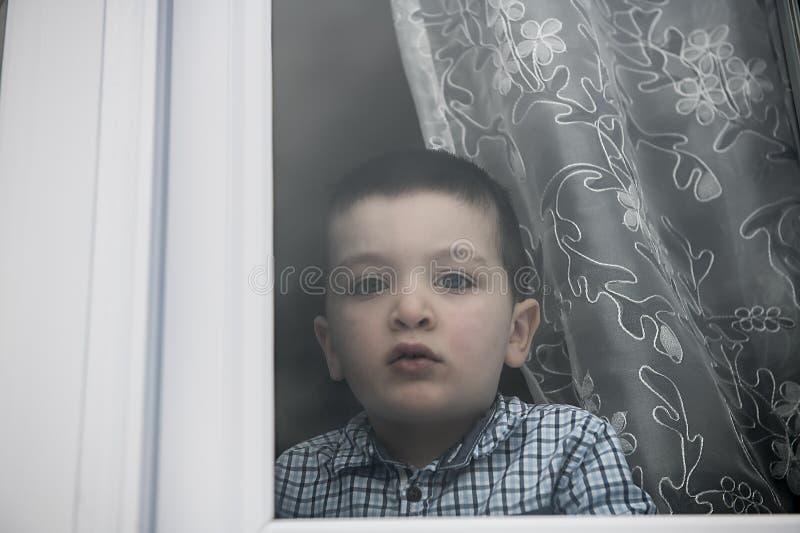 Rapaz pequeno triste atrás de um olhar da janela triste fotos de stock