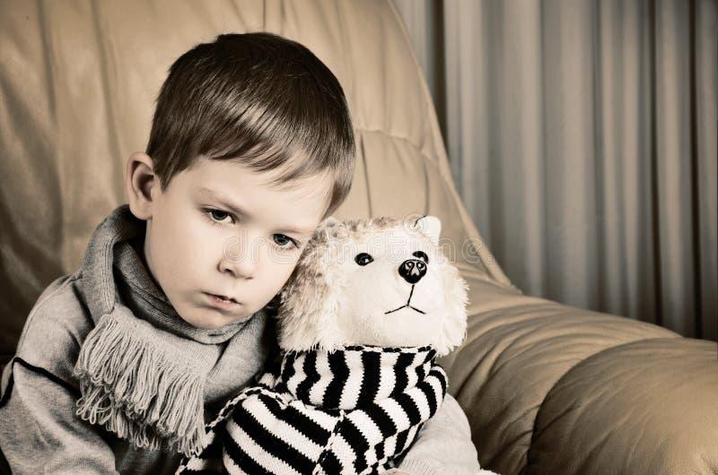 Rapaz pequeno triste matizado da imagem que abraça o cão de brinquedo imagens de stock