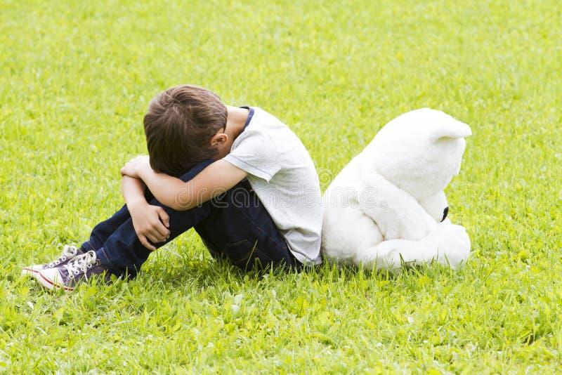 Rapaz pequeno triste que senta-se com um urso de peluche Girado afastado e abaixado suas cabeças Tristeza, medo, frustração, conc imagem de stock royalty free