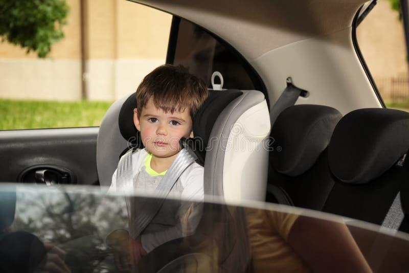 Rapaz pequeno triste que senta-se no assento da segurança apenas dentro do carro fotografia de stock