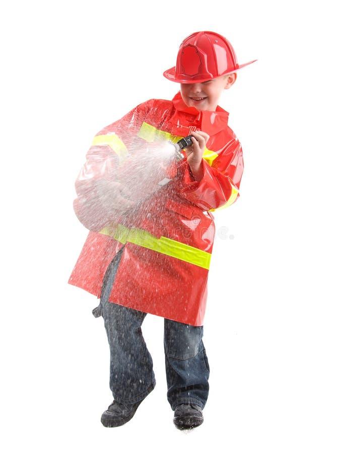 Rapaz pequeno vestido acima como do sapador-bombeiro imagens de stock royalty free