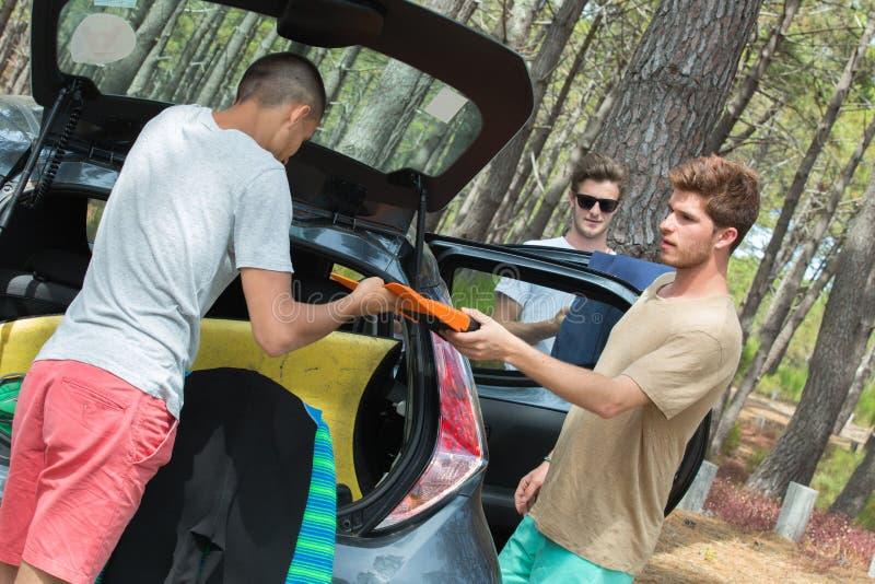 Rapazes adolescentes que descarregam o equipamento da ressaca de seu veículo imagem de stock