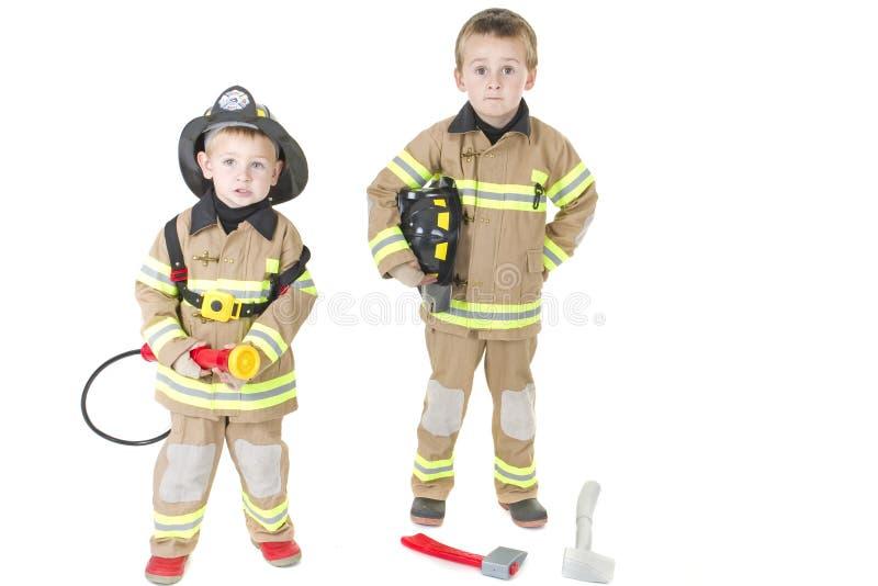 Rapazes pequenos bonitos no equipamento do bombeiro imagens de stock