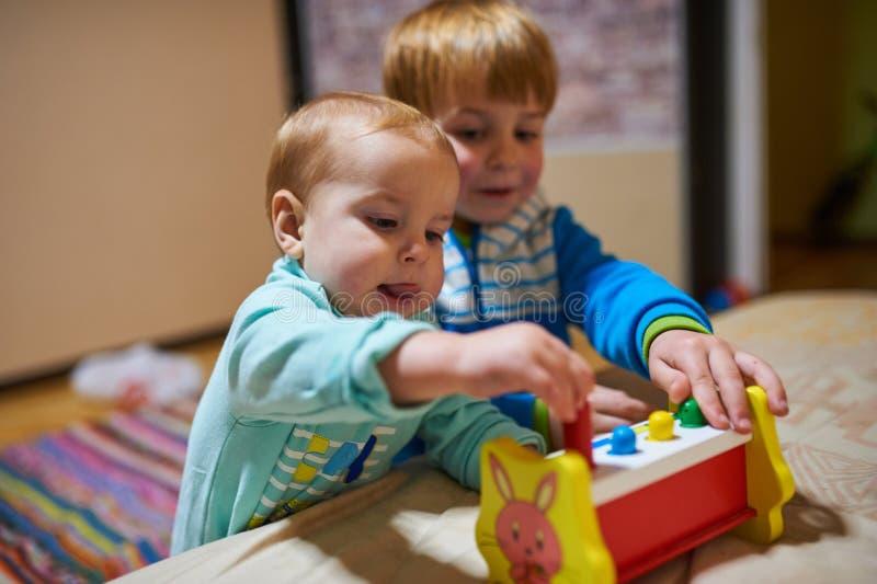 Rapazes pequenos bonitos que jogam com os brinquedos pela casa imagens de stock royalty free