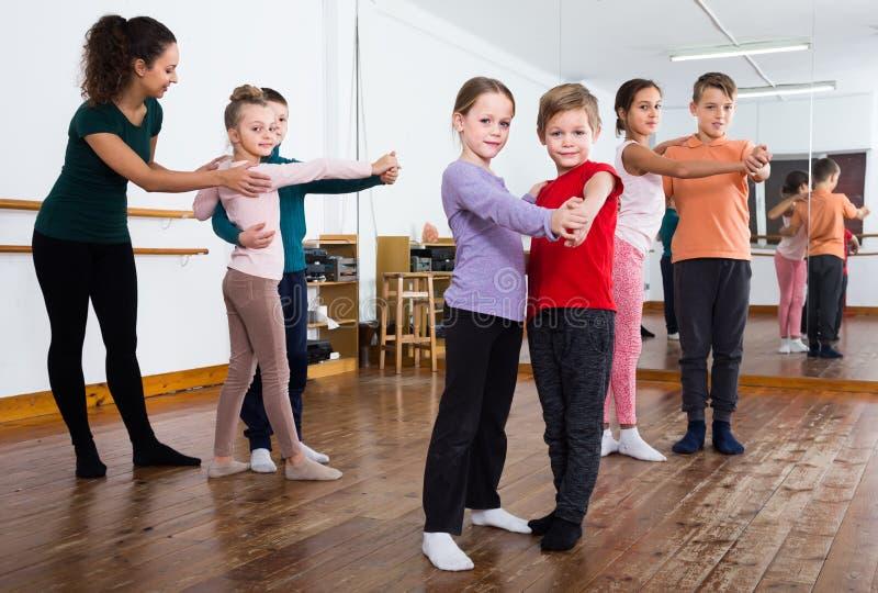 Rapazes pequenos contentes e meninas que dançam a dança dos pares imagem de stock royalty free