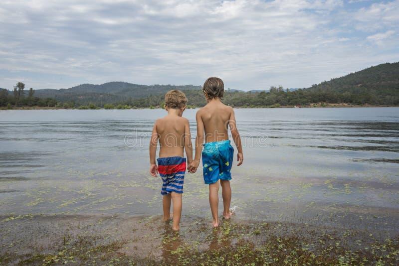 Rapazes pequenos no lago da montanha fotos de stock royalty free