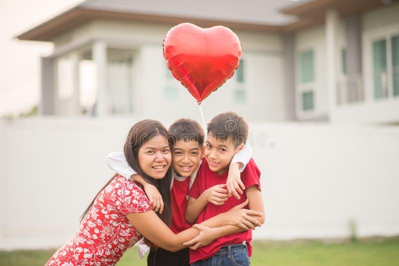 Rapazes pequenos que dão o coração do balão a seu amor de mãe fotos de stock royalty free