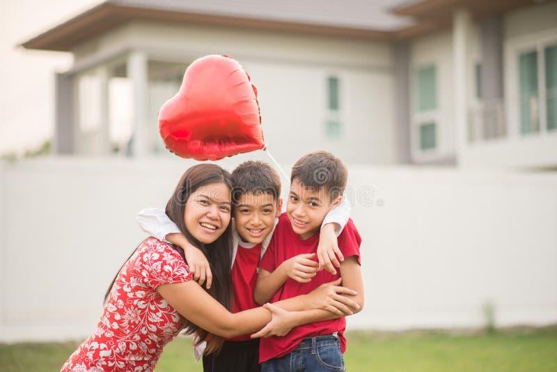 Rapazes pequenos que dão o coração do balão a seu amor de mãe fotografia de stock
